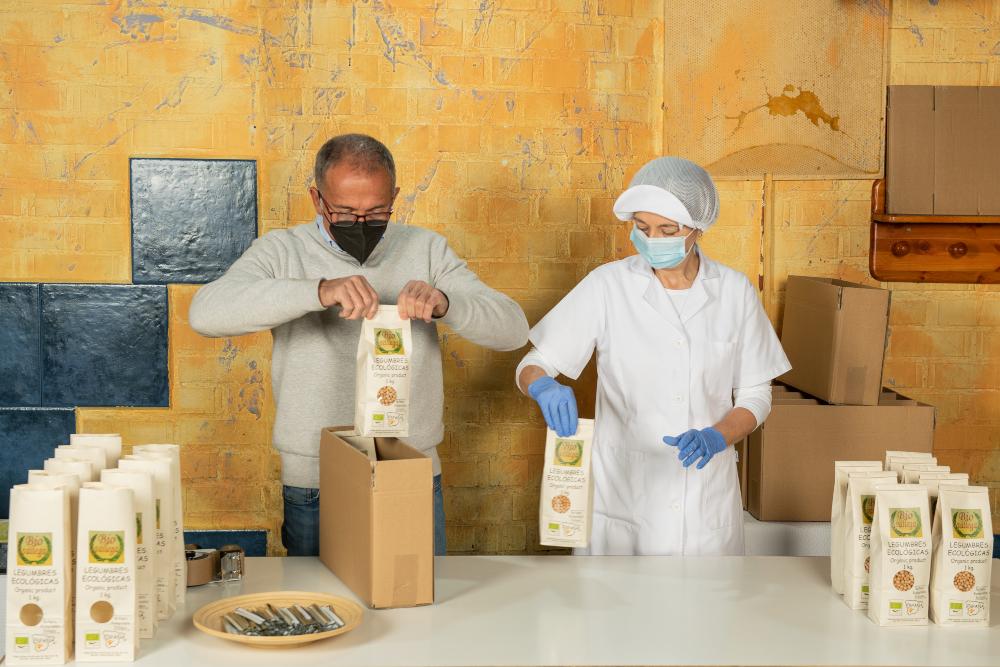Dos personas empaquetando bolsas de garbanzos en una caja de cartón