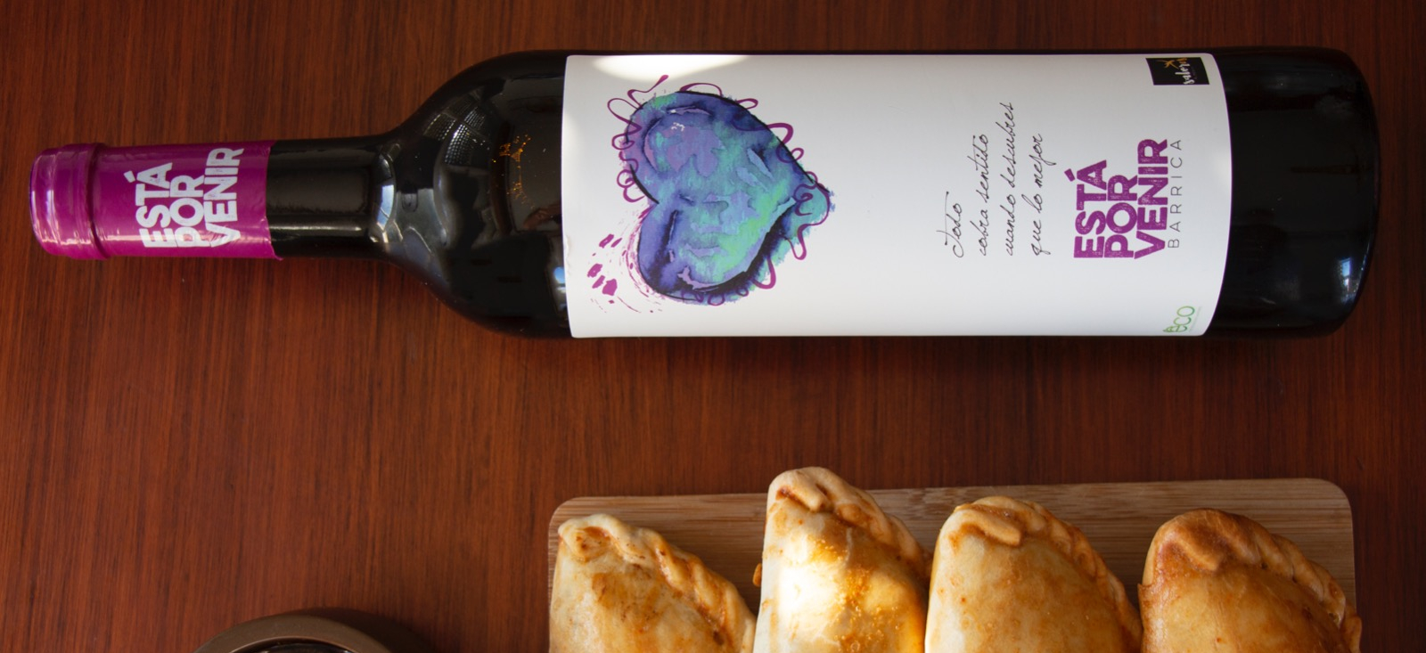 Bottle of red wine with empanadas on a board