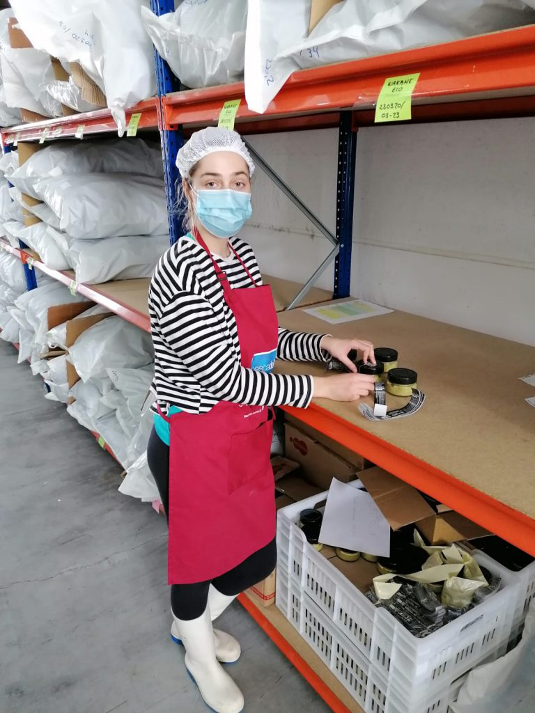 A person with a mask and apron in a warehouse